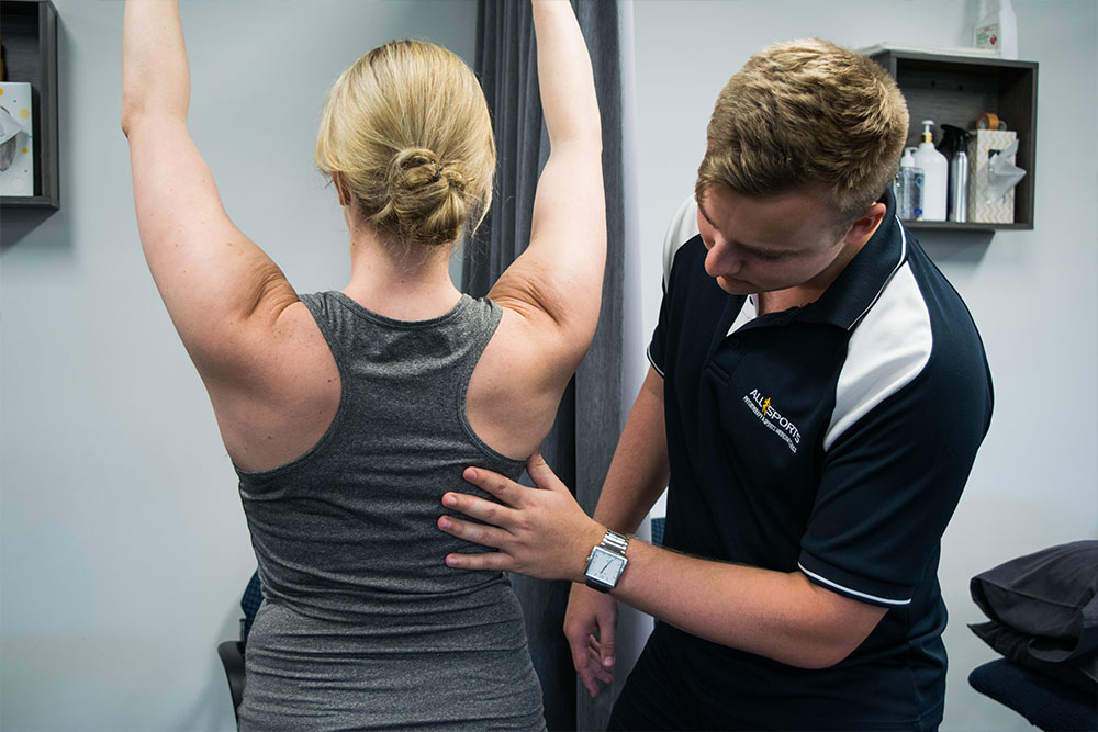 Physiotherapist inspecting woman's back muscle