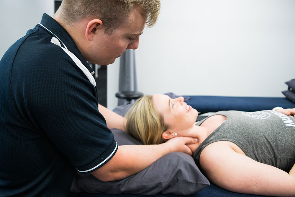 Allied health professional treating neck pain