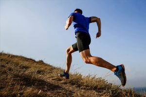 Male runner running up grassy hill