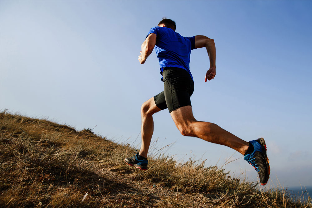 Male runner running up grassy hill - Allsports Physiotherapy