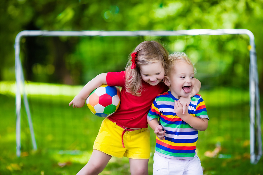 Two happy children playing football outdoors