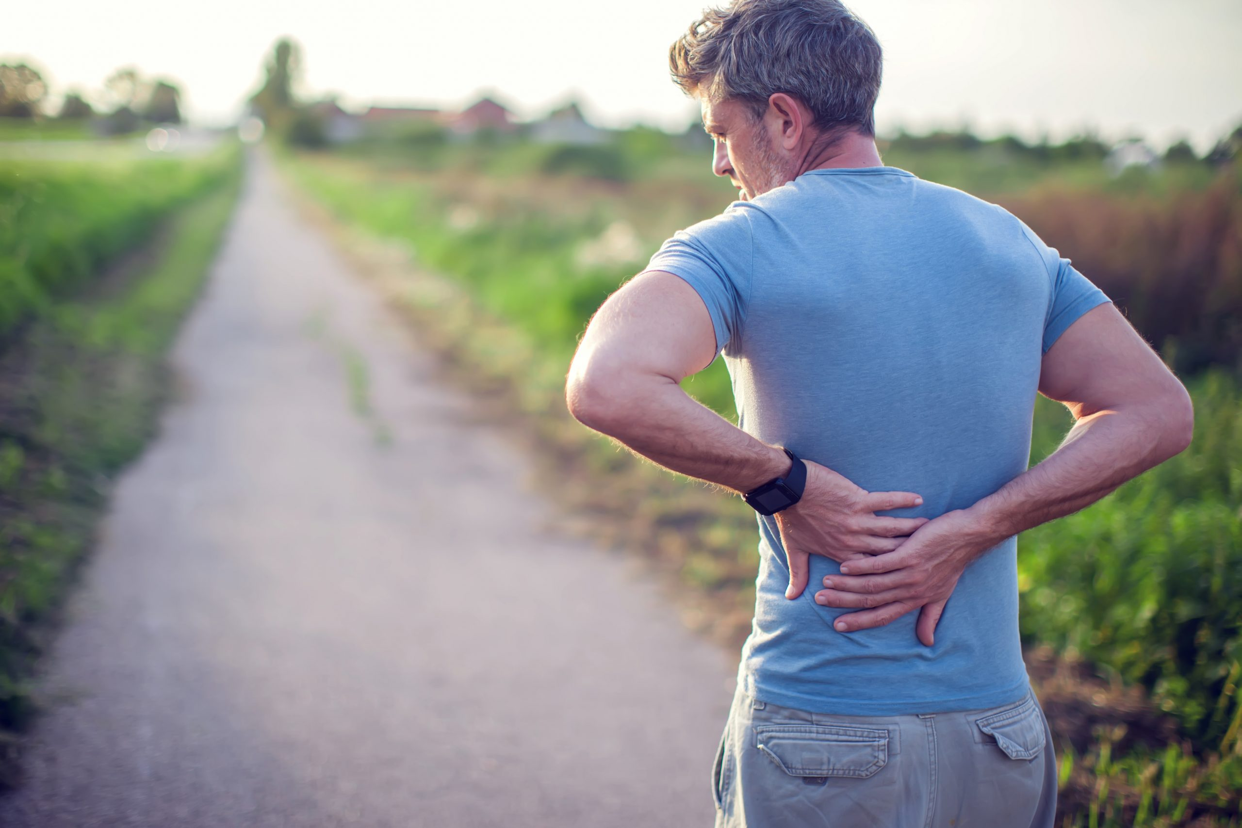 Man on a road holding his back from back pain