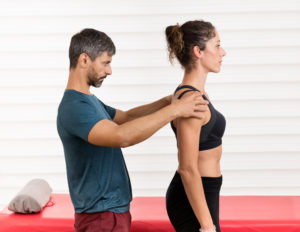 Male osteopath doing a postural evaluation on a young female patient assessing the alignment of her vertebrae and spine in an alternative medicine and healthcare concept